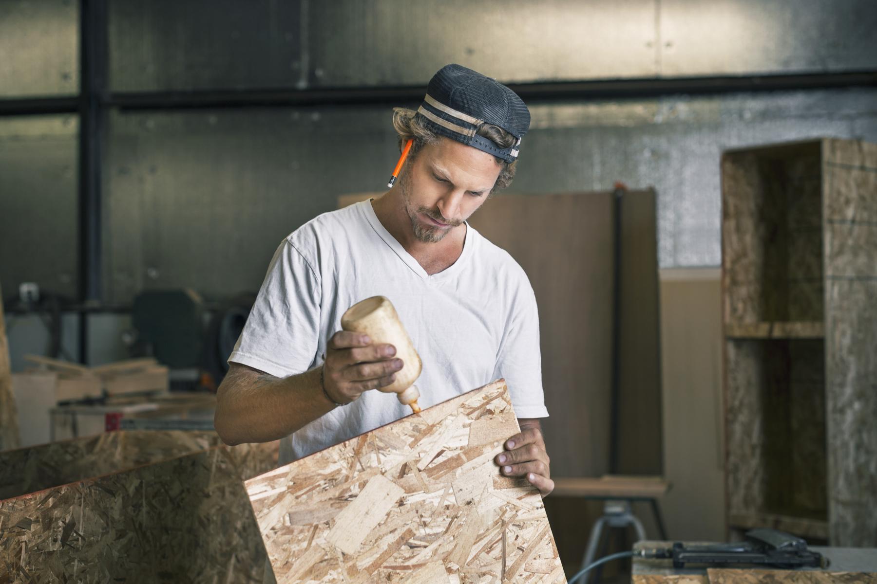Handwerker trägt Kleber auf Bodenplatte auf